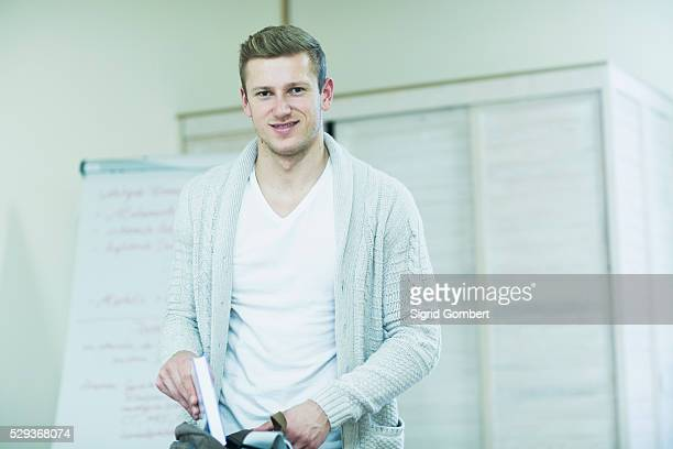 young male teacher putting book in bag, freiburg im breisgau, baden-w��rttemberg, germany - sigrid gombert stock pictures, royalty-free photos & images