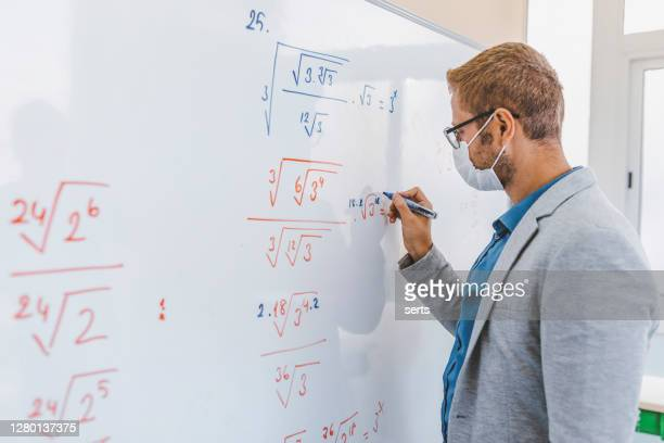 young male teacher with face mask writing on blackboard in classroom - instructor stock pictures, royalty-free photos & images