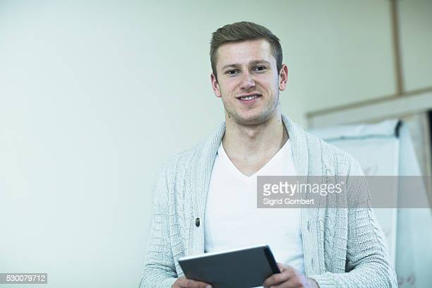 young male teacher working on a digital tablet in classroom, freiburg im breisgau, baden-w��rttemberg, germany - sigrid gombert fotografías e imágenes de stock