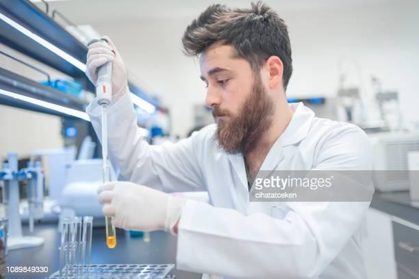 young male tech or scientist loads sample with automatic pipette - químico imagens e fotografias de stock