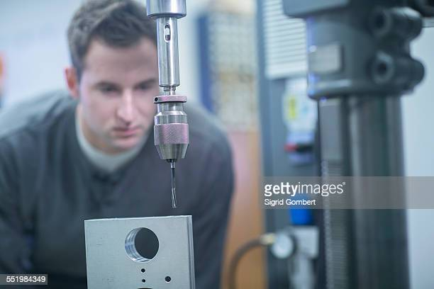 young male technician checking metal drill machine in workshop - sigrid gombert stock pictures, royalty-free photos & images