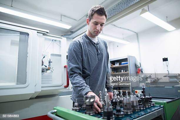 young male technician choosing drill bit in workshop - sigrid gombert stock-fotos und bilder