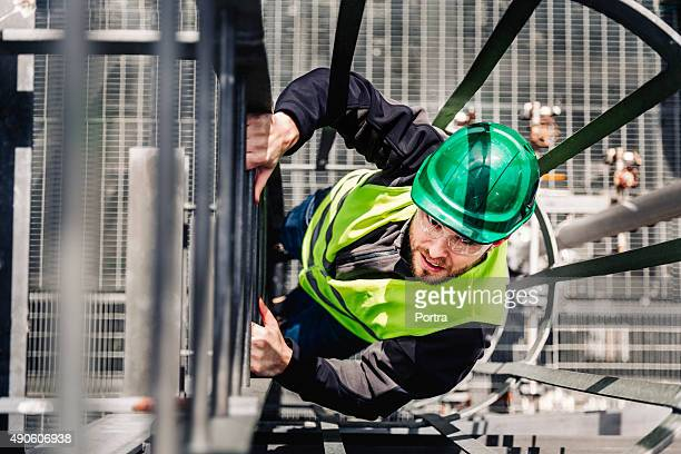 Young male technician climbing ladder in industry