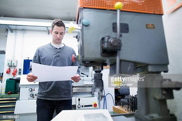 young male technician looking at blueprint in workshop - sigrid gombert stock-fotos und bilder