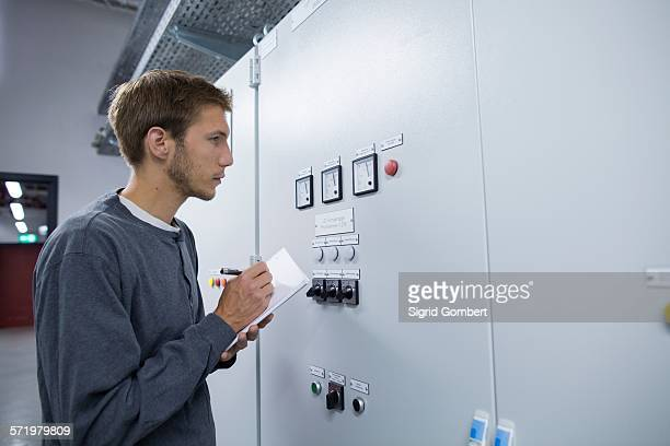 young male technician making notes in technical room - sigrid gombert stockfoto's en -beelden
