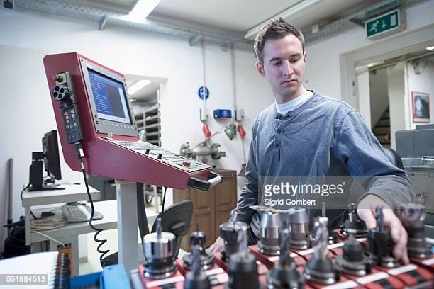 young male technician picking drill bit in workshop - sigrid gombert stock-fotos und bilder