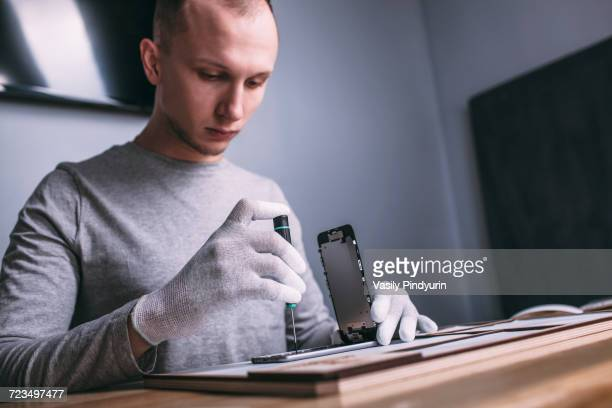 Young male technician repairing smart phone at electronics store