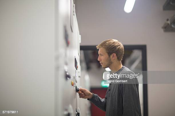 young male technician turning switch in technical room - sigrid gombert stockfoto's en -beelden
