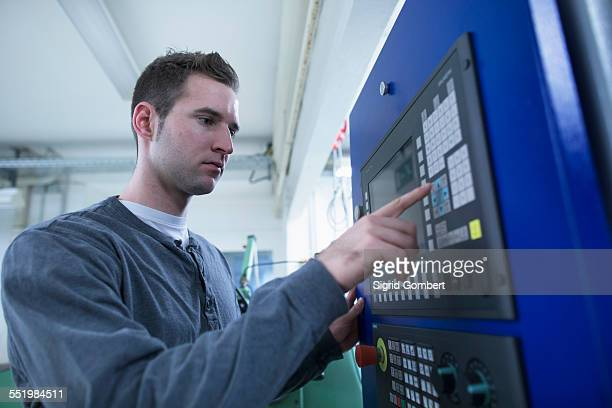 young male technician using control panel for equipment in workshop - sigrid gombert stock-fotos und bilder