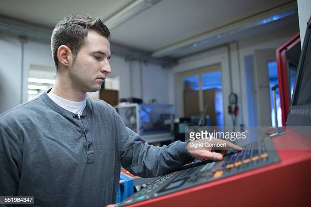 young male technician using control panel for machine in workshop - sigrid gombert stock-fotos und bilder