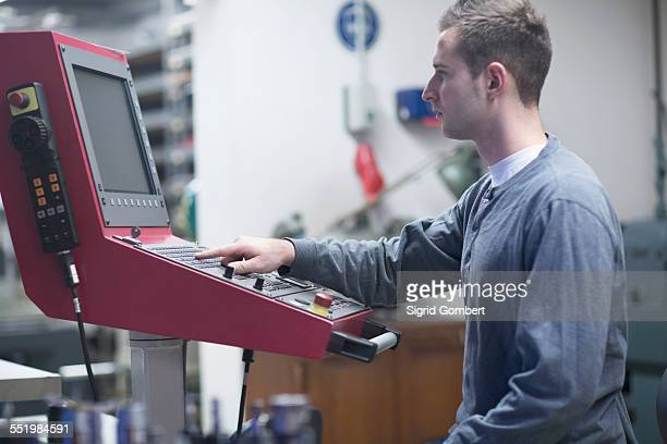 young male technician using control panel in workshop - sigrid gombert stock-fotos und bilder