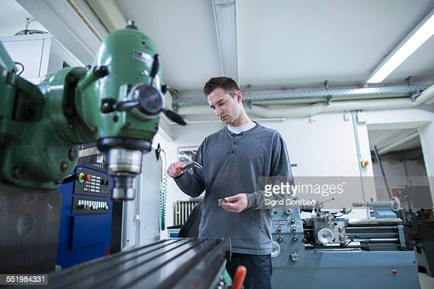 young male technician using vernier caliper in workshop - sigrid gombert stock-fotos und bilder
