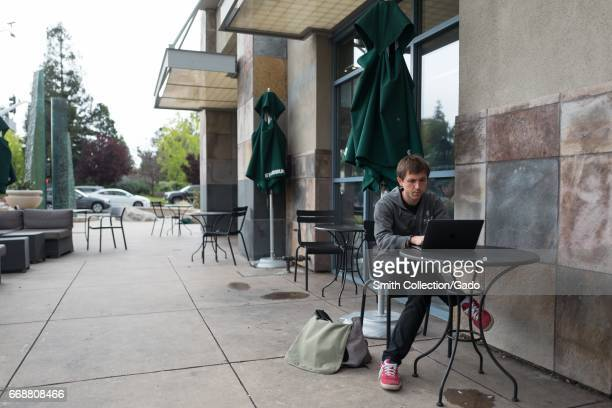 A young male technology worker wearing a hoodie sits outside at a Starbucks and works on a laptop near the Googleplex headquarters of Google Inc in...