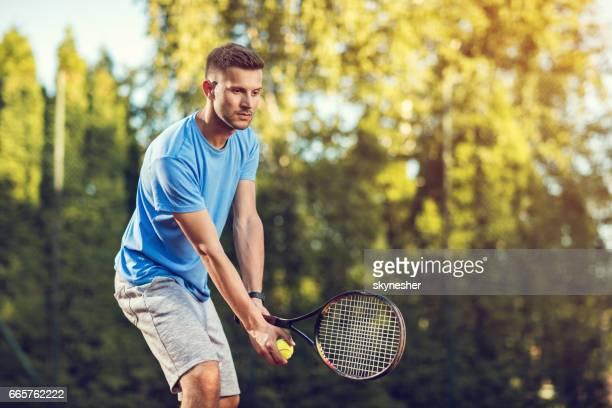 ボールをサーブする若い男性のテニス プレーヤーです。