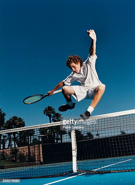 young male tennis player jumping net - tennis racquet stock pictures, royalty-free photos & images