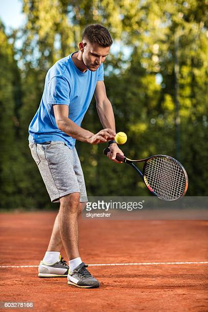 Young male tennis player preparing for serving on the court.