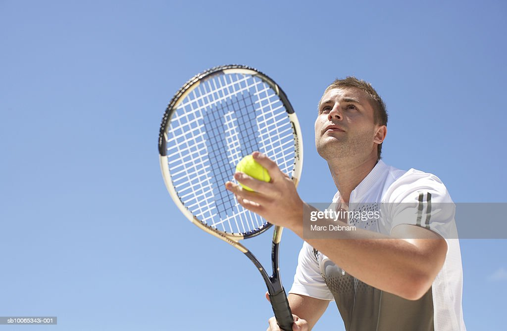 Young male tennis player serving, outdoors : Foto stock