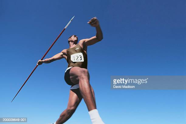 young male throwing javelin, low angle view (digital enhancement) - javelin stock pictures, royalty-free photos & images