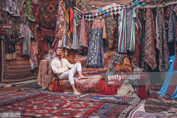 junge männliche touristin genießt im traditionellen teppichgeschäft in kappadokien, türkei - thron stock-fotos und bilder