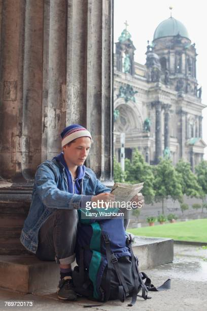 Young male tourist sitting with map at Altes Museum against Berlin Cathedral, Germany