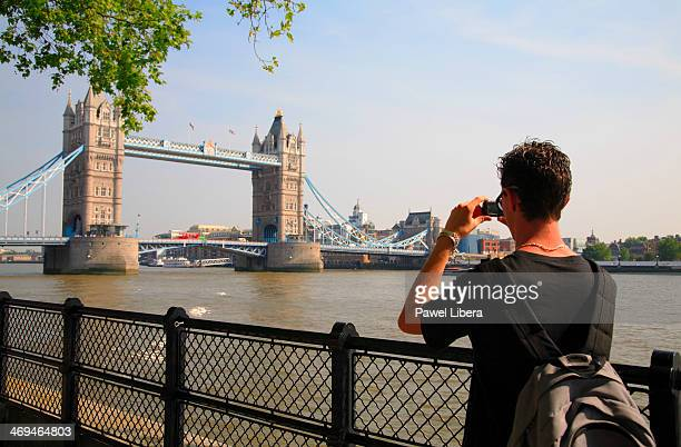 Young male tourist taking photographs with a compact digital camera of Tower Bridge in London