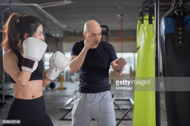 A young male trainer is coaching a young female practicing boxing