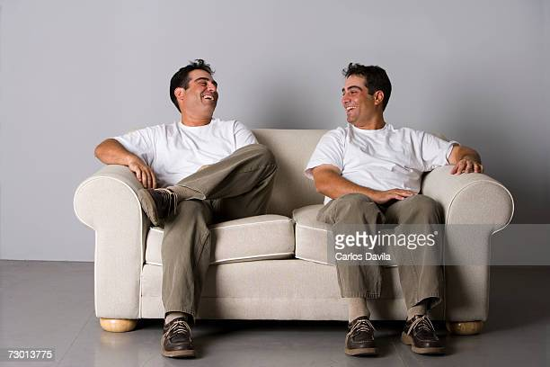 Young male twins sitting on sofa, laughing