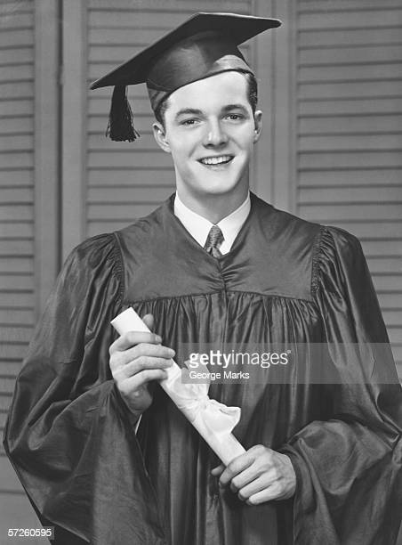 Young male university graduate holding diploma, (B&W), portrait