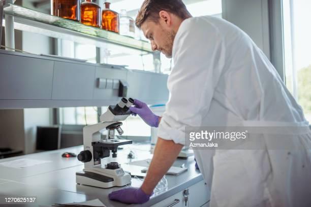 研究室で顕微鏡を用いた若手男子大学生 - 袖 ストックフォトと画像
