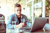 young male using portable devices while