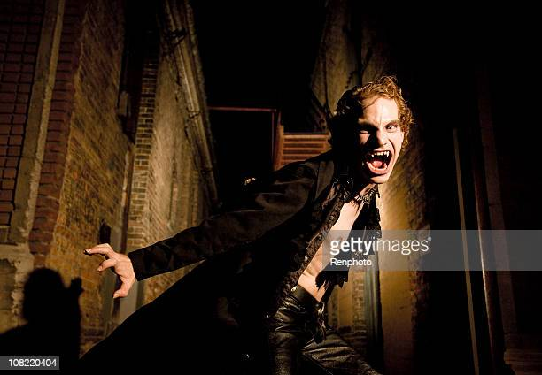 young male vampire hissing at the camera - vampire stock pictures, royalty-free photos & images
