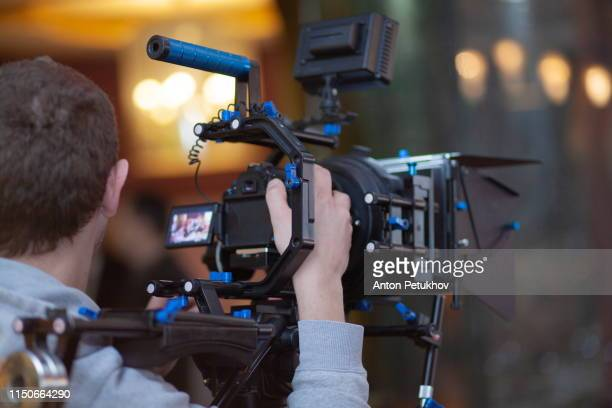 young male video cameraman, photographer, shoots video or takes a photo on the camera. - filmregisseur stock-fotos und bilder