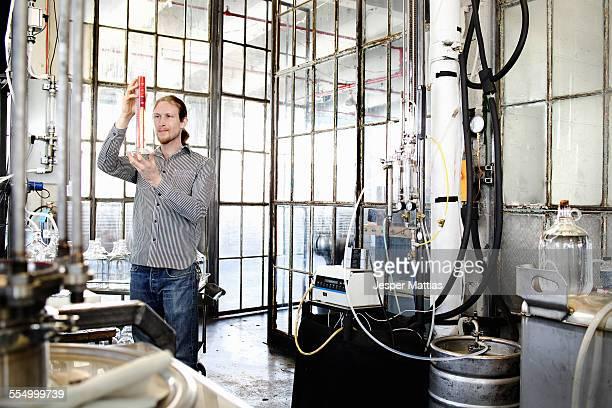 Young male vodka distiller measuring liquid in cylinder in distillery workshop