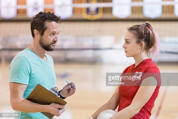 young male volleyball coach talking to a young girl player - high school volleyball stock photos and pictures