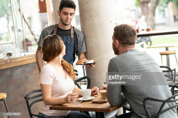 young male waiter bringing an order to couple customer enjoying a warm drink at the restaurant - spoil system stock pictures, royalty-free photos & images