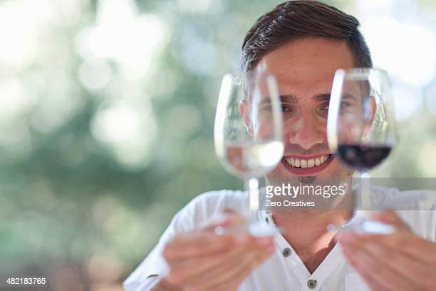 Young male waiter holding up glasses of red and white wines