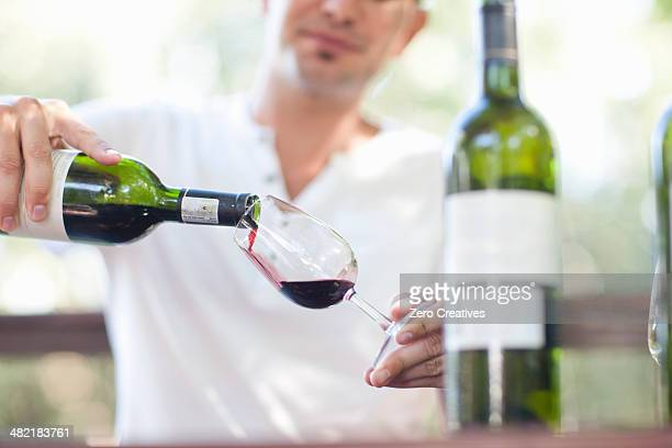 Young male waiter pouring red wine at vineyard bar