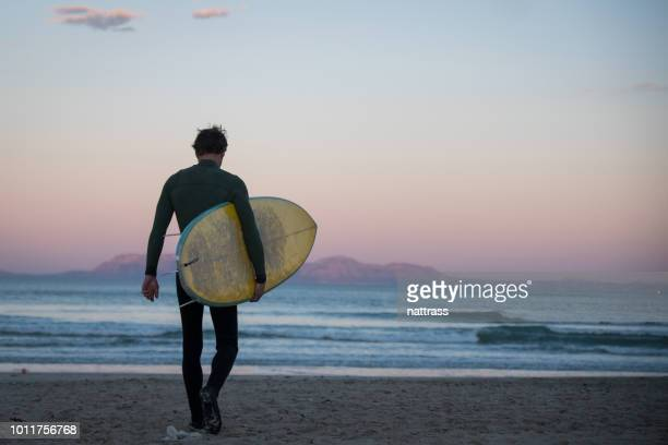 young male walks down the beach with his surfboard - only mid adult men stock pictures, royalty-free photos & images