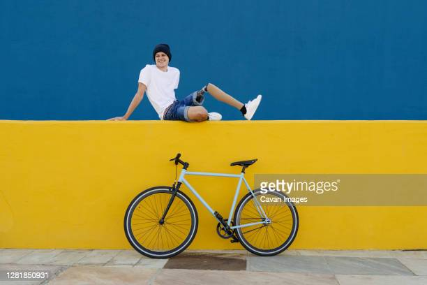 young male with disability sitting near bike - disability stock pictures, royalty-free photos & images