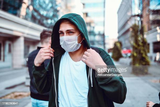 young male with mask as a sign of protest against air pollution - protestor mask stock pictures, royalty-free photos & images