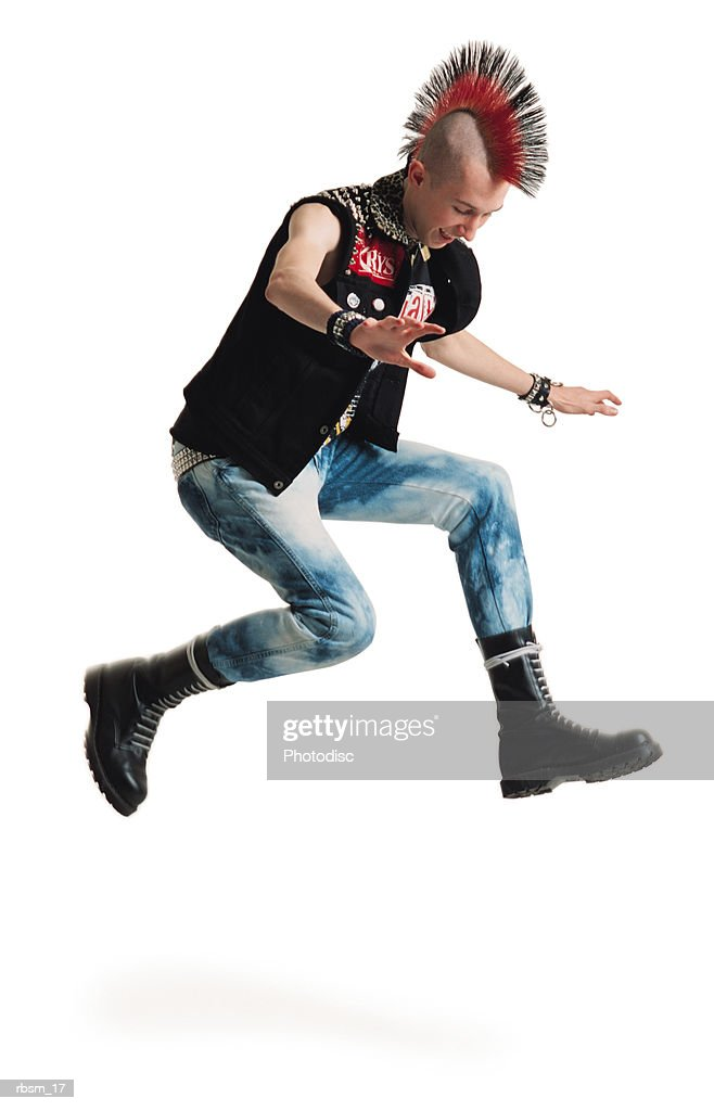 young male with mohawk studded vest bleached jeans big black boots jumps in the air with arms out : Foto de stock