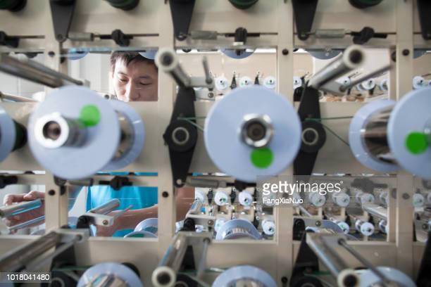 joven trabajador de sexo masculino en una fábrica en dongguan, china - provincia de guangdong fotografías e imágenes de stock
