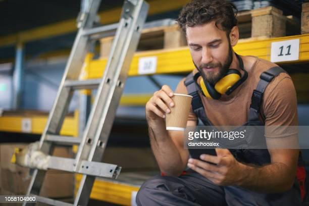 junge männliche arbeiter im lager überprüfen zeug - handwerker stock-fotos und bilder