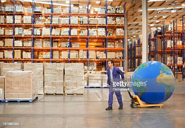 Young male worker pulling hand truck with large blue ball in warehouse