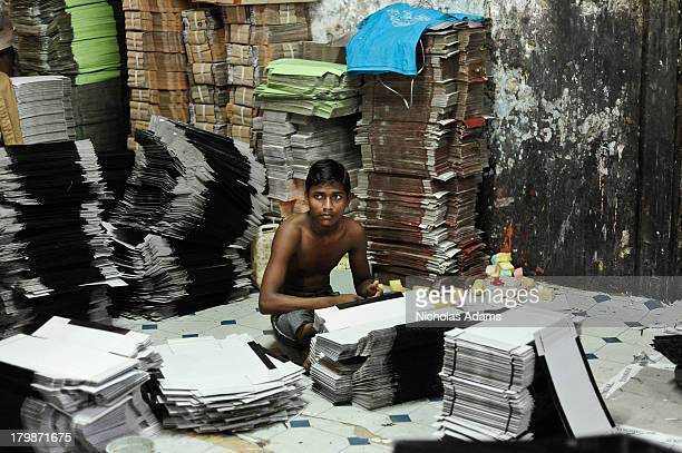 Young male works constructing shoe boxes in a factory/ sweatshop in Dharavi Slum in Mumbai