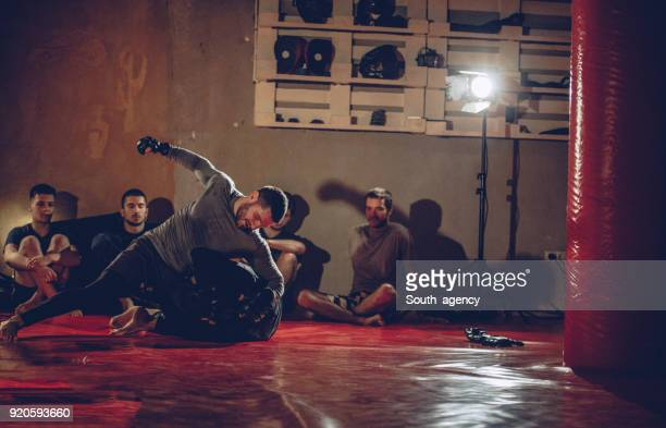 young males practicing mixed martial arts in the gym - mixed martial arts stock pictures, royalty-free photos & images