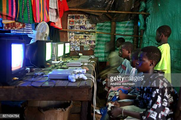 Young Malian teenagers play a football game on Sony Playstation game consoles at a market stall in the local market of Bamako Mali