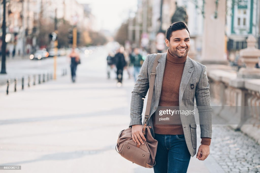 Young mam walking outdoors in the city : Stock Photo