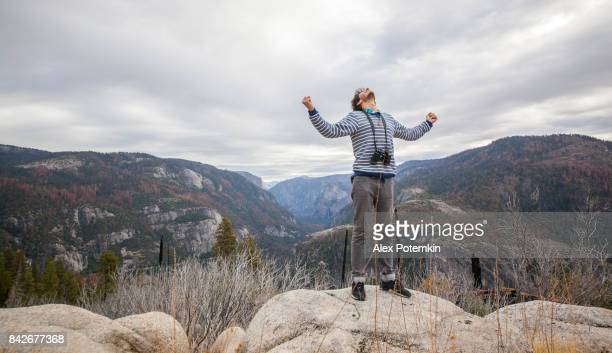 Young man, 25-years-old traveling hipster, meditating and observing the nature from the elevated rocky point near by Devil Dance Floor in the Yosemite National Park