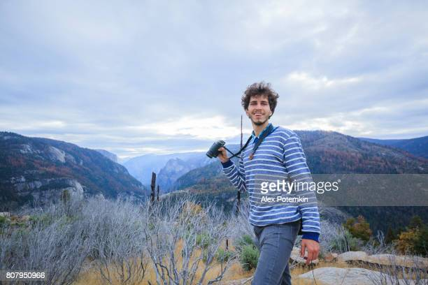 Young man, 25-years-old traveling hipster, observing the nature with the binocular from the elevated rocky point near by Devil Dance Floor in the Yosemite National Park